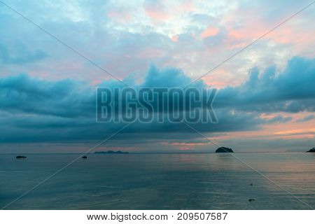 Early Sunrise With Low Clouds Above The Calm Sea