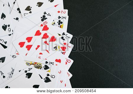 Lot of dusty old playing cards. set black cards on the black ground, playing card. playing cards scattered on a table, the concept of passion, risk.