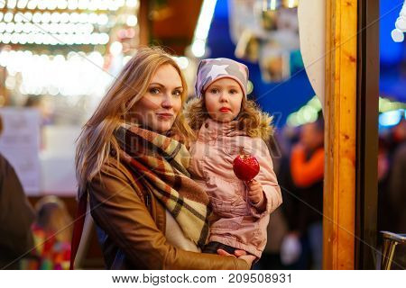 Beatiful woman and little kid girl eating crystallized sugared apple on German Christmas market. Happy family, mother and daughter in winter clothes with lights on background. Tradition, holiday concept