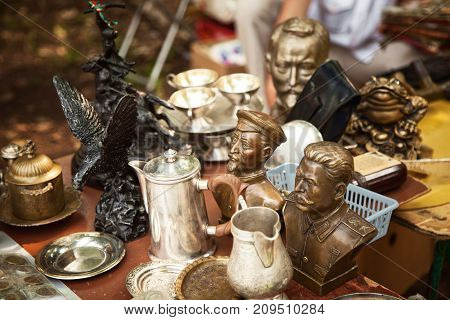 Khabarovsk Russia - July 27 2014: USSR famous historic persons busts and metal tableware at a flea market. Many old vintage things at a garage sale