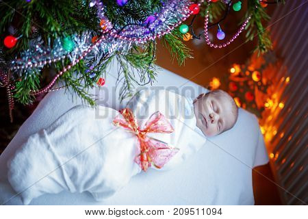 One week old newborn baby wrapped in blanket near Christmas tree with colorful garland lights on background. Closeup of cute child, little baby sleeping. Family, Xmas, birth, new life