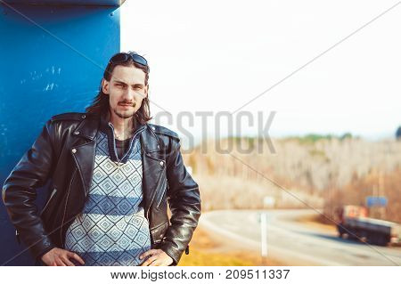 Male biker in a leather jacket and bandana puts on sunglasses and looking at the camera. Motorcyclist in leather jacket puts on sunglasses.