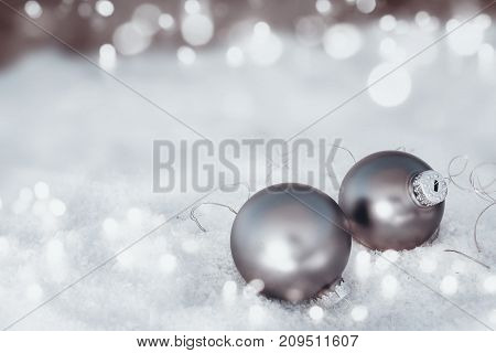 Frosty snow bokeh background with a light chain and silver christmas balls for congratulations