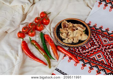 mushrooms on a plate of tomatoes pepper and Ukrainian embroidery mushrooms sauteed in small white bowl