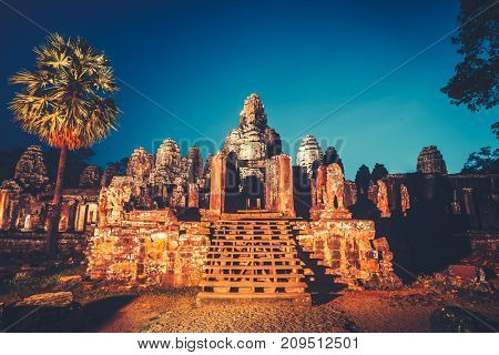 Angkor Wat Temple in Cambodia is the largest religious complex, inscribed on UNESCO World Heritage List. Ancient Khmer architecture. Orange ancient ruins against blue night sky. Retro vintage toning