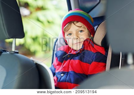 Portrait of preschool kid boy sitting in car. Child in safety car seat with belt. Safe travel with kids and traffic laws concept. Little boy in colorful autumn and winter fashion clothes