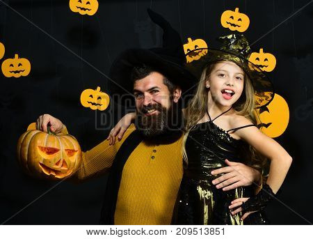 Wizard And Little Witch In Black Hats Hold Pumpkin.