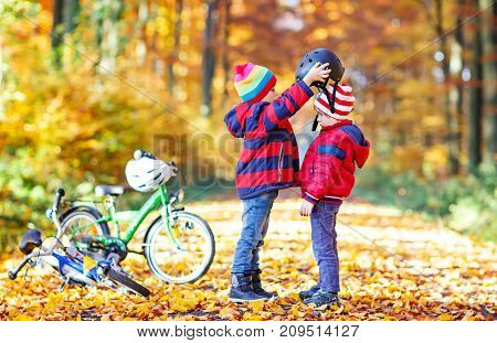 Two little kids boys, best friends in autumn forest. Older brother helping younger child putting safe helmet before cycling on sunny fall day in nature. Safety, sports, leisure with kids concept.