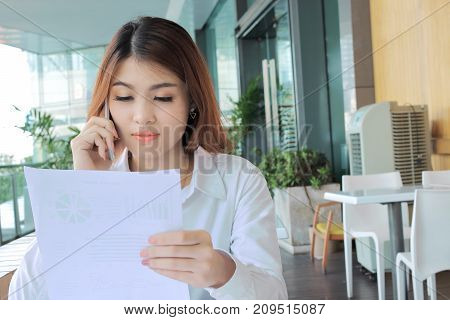 Portrait of attractive young Asian business woman talking on phone against holding document files on her hand in office.