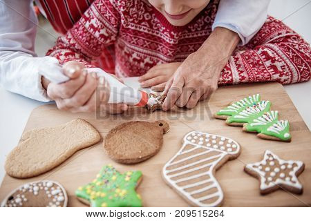 Top view close up of joyful girl squeezing cream on traditional Christmas cookie together with her granny. Focus on their hands