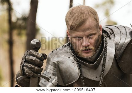 Tired Knight In Armour After Battle On Forest Background.