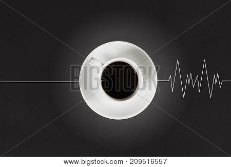 Invigorating coffee in the morning awakens the head and causes the heart to beat. Coffee and cardiogram on black background