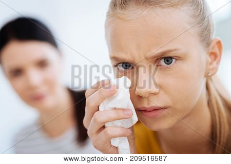 Negative emotions. Portrait of a sad unhappy crying woman holding a tissue and wiping her tears while looking at you