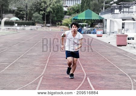 Young healthy Asian man running on racetrack at athletics stadium.