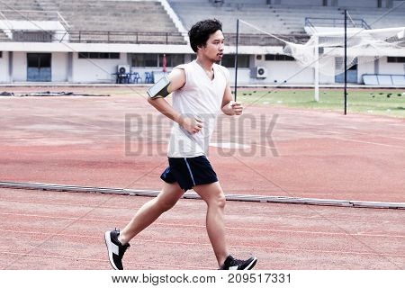 Dramatic toned image of handsome athlete Asian man running on racetrack in stadium. Healthy active lifestyle concept.
