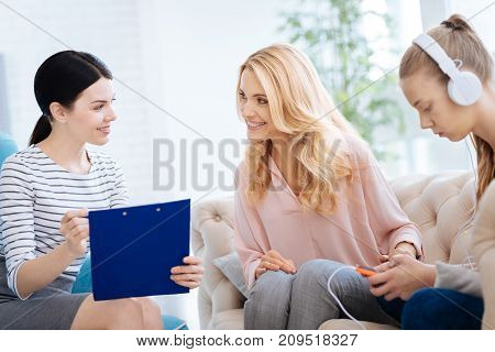 Helpful therapy. Cheerful positive delighted woman looking at the psychologist and smiling while being thankful for help
