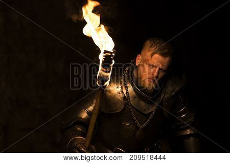 Knight With A Torch At Night On A Wall Background