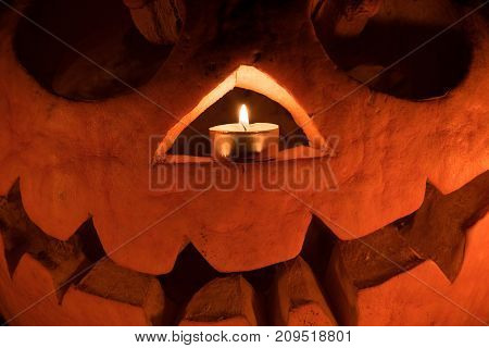 Orange pumpkin as a head with carved eyes and a smile with burning candles on a black background with a garland to the Halloween party