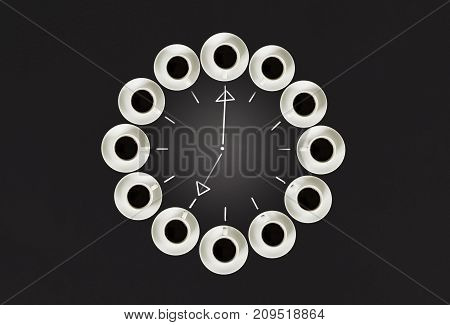 Cups with coffee, stacked in a circle. Clock consist of twenty cups. Drawing sticks lancets Time. Alarm clock. Black background. Concept time to coffee