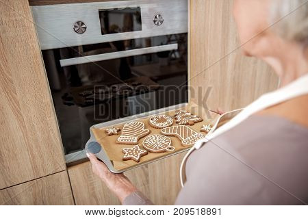 Rear view close up of senior lady putting tray with Christmas cookies into oven. She is standing in kitchen