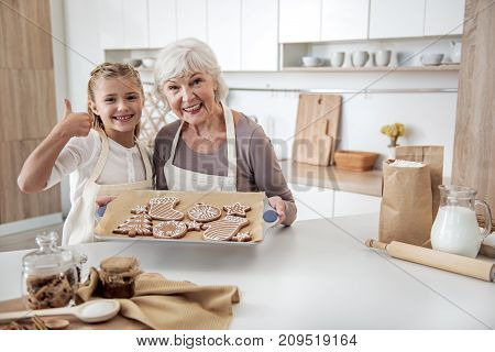 Our cookies are great. Portrait of joyful girl giving thumb up while her granny is holding tray with pastry. They are standing in kitchen and smiling