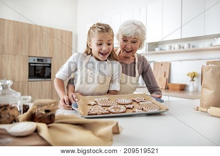 Portrait of excited girl looking at self-made cookies with joy. Her granny is holding a tray and embracing kid with proud. Family is laughing