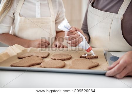Close up of hands of senior woman squeezing white cream from tube on sweet pastry. Granddaughter is standing near her in kitchen