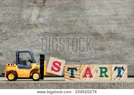 Yellow plastic forklift hold letter S to complete word start on wood background