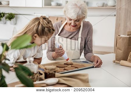 Cheerful old woman is squeezing cream on fresh baked cookie in the kitchen. Girl is watching this process with interest and smiling