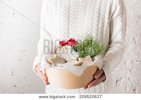 Female hands holding a box with Christmas cookies. The festive concept. Front view. A bright background.Copy space