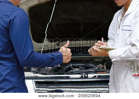 Mechanic and customer between repairing engine of car at auto service garage.