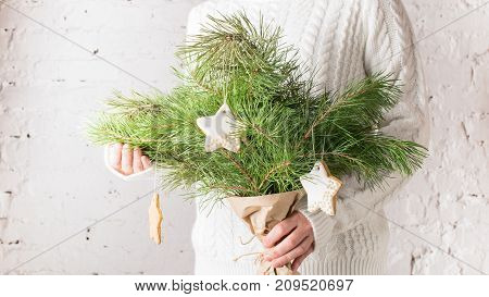 Female hands holding a Christmas bouquet of branches of spruce decorated with a pastry star. New year. Settle background kinfolk . Copy space