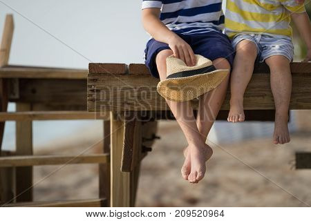 all children sitting on the wooden pier and enjoying summer day on the beach. Bare feet of boys. Vacation by the sea. Outdoors. Siblings. Brothers by the ocean.