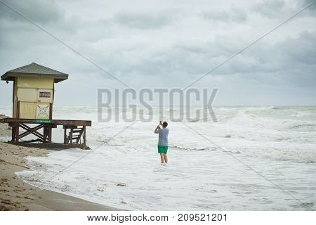 Miami USA October 05 2017: Man taking photo of beach lifeguard station or stand with his smartphone on the shore of the ocean. Tourist standing in sea water photographing tower on bad weather day