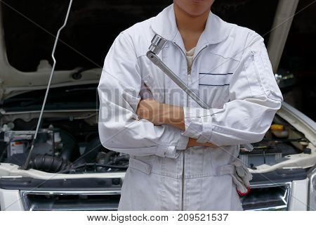 Portrait of professional young mechanic man in uniform holding wrench against car in open hood at the repair garage.