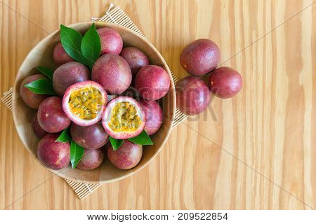 Fresh passion fruit in wood bowl on wood table in top view flat lay with copy space for background or wallpaper. Ripe passion fruit so sweet and sour. Tropical fruit. Passion fruit background with copy space concept.