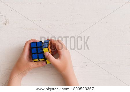 Moscow Russia August 24 2017: Rubik's cube in child's hands closeup white wooden background. Boy holding Rubik's cube and playing with it.