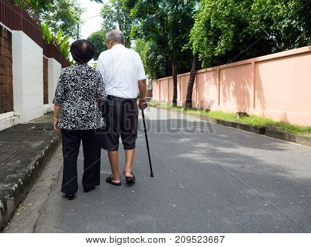 Happy romantic senior asian couple walking and holding hands on the road at the village. Concept of senior couple and take care of each other