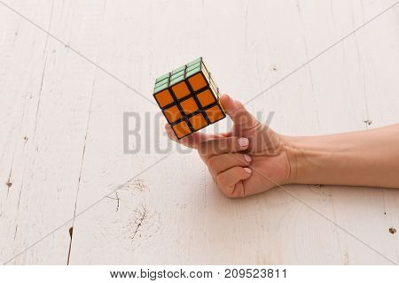 Moscow Russia August 24 2017: Rubik's cube in woman's hand closeup white wooden background. Girl holding Rubik's cube and playing with it.