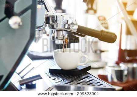 coffee machine pouring coffee into white coffee cup.Cappuccino pouring from professional coffee machine brewing