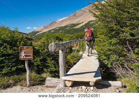 Man walking on a wooden bridge trough the mountains / One person with a backpack crossing a bridge of wood in the wild