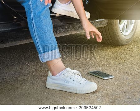 Women picking up smart phone that fall on the floor while stepping down from the car