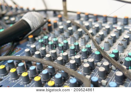 Close Up Of Button Of Sound Mixed With Blurred Microphone.