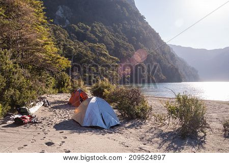 Two tents in a campsite near a lagoon in the mountain / Camping gear isolated / Camping next to a lake in the morning or the afternoon