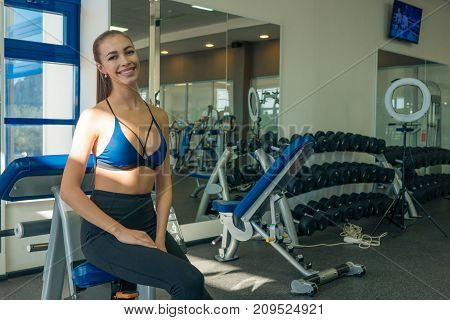 Young beautiful athletic girl posing in the gym