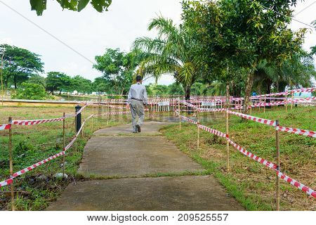 Cement Path Way With Red And White Tripped Tape Fence For Barricades Or Restrcited Zones Or Forbidde