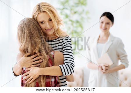 Warm feelings. Beautiful delighted caring woman smiling and hugging her daughter while expressing her love to her