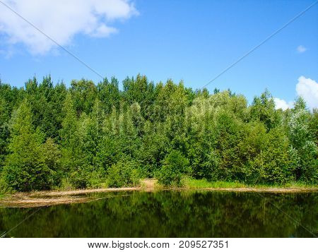 Russian nature. Green forest. Travel in Russia. Lake in summer forest. Green trees reflected in the lake in Russian. Summer landscape. Russian forest in summer in Sunny day. Nature Reserve. The lake in Russia