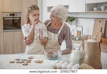 Joyful girl is showing self-made cookie to her granny. She is standing near table with food ingredients in kitchen