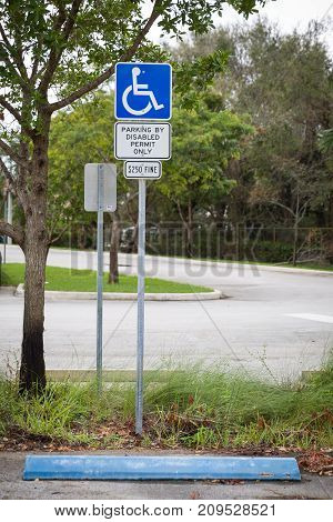 Disabled parking space wheelchair sign symbols and fine notice on the parking place in the park.